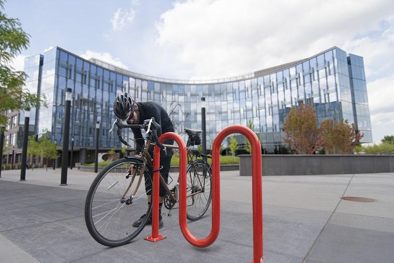 cyclist standing next to bike rack