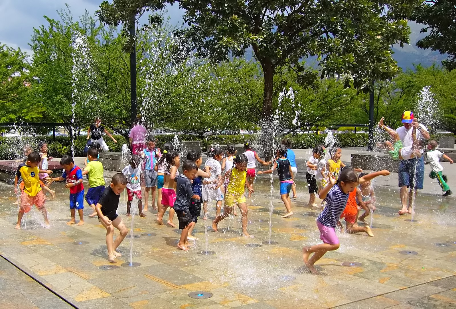 city children playing on water playground equipment